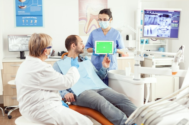 Enfermera médica sosteniendo simulacros de tableta chroma key de pantalla verde con pantalla aislada durante la consulta de somatología