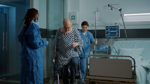 Enfermera y médico afroamericano ayudando a asiento paciente enfermo