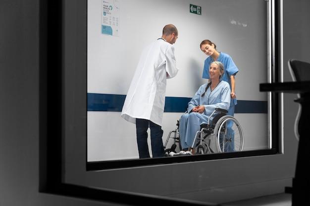 Enfermera y médico de tiro completo revisando al paciente