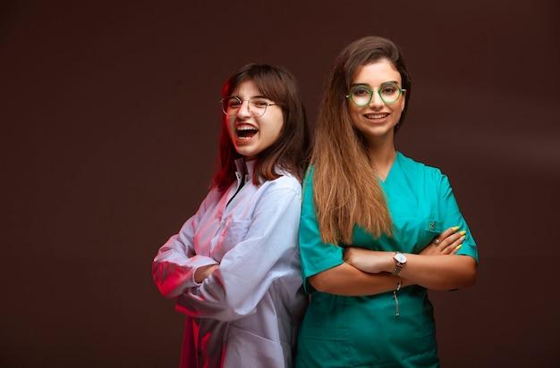 La enfermera y el médico se ven profesionales y sonrientes.