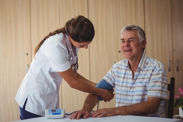 Enfermera midiendo la presión sanguínea de un hombre mayor
