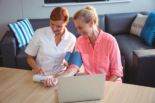 Enfermera midiendo la presión sanguínea de una mujer mayor