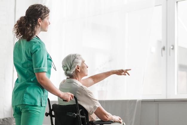 Enfermera mirando senior mujer sentada en silla de ruedas apuntando hacia la ventana