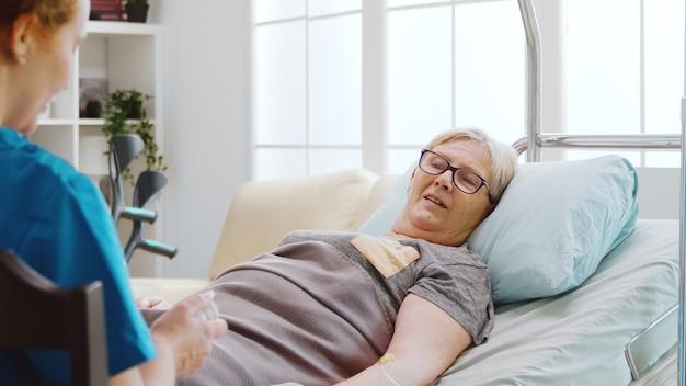Enfermera mostrando a una anciana qué píldoras tomar mientras ella está acostada en la cama de un hospital en una casa de retiro