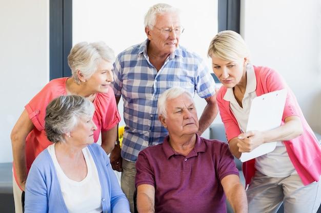 Enfermera mostrando portapapeles a personas mayores