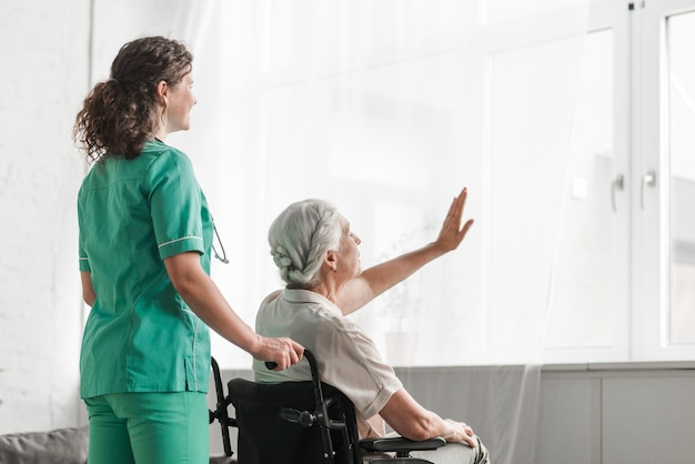 Enfermera con la mujer mayor que se sienta en silla de ruedas que toca la cortina blanca