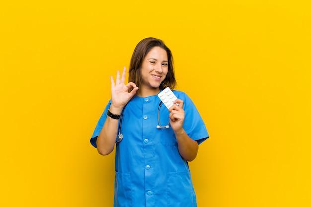 Enfermera mujer con pils contra la pared naranja