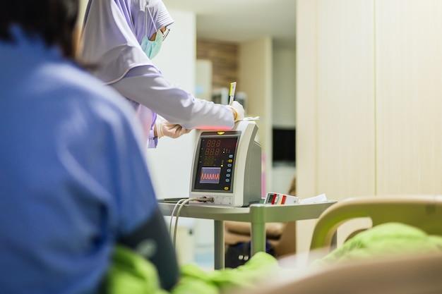 Enfermera musulmana escribiendo en el portapapeles midiendo la presión arterial del paciente mayor