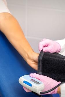 Enfermera o doctora pone tonómetro en el brazo de una mujer joven en el hospital