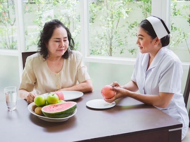 La enfermera está pelando manzanas para los ancianos.
