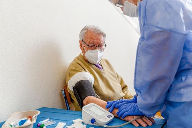 Enfermera protegida por coronavirus toma el manguito de presión arterial de un anciano