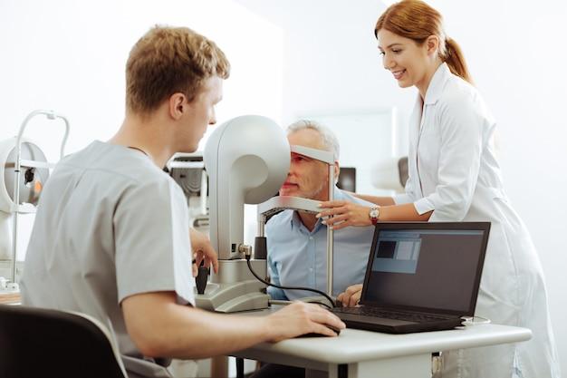 Enfermera que ayuda al paciente. agradable y servicial enfermera que ayuda al paciente a visitar al especialista en ojos en una clínica privada