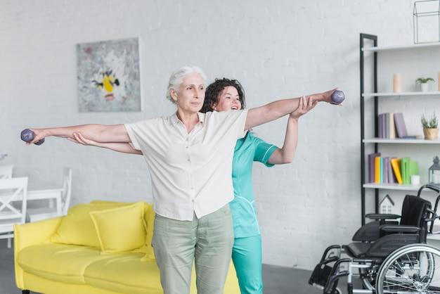 Enfermera que ayuda a su paciente femenino mayor que ejercita con pesas de gimnasia