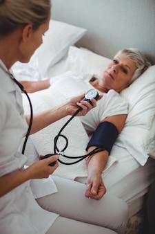 Enfermera que controla la presión arterial de la mujer mayor