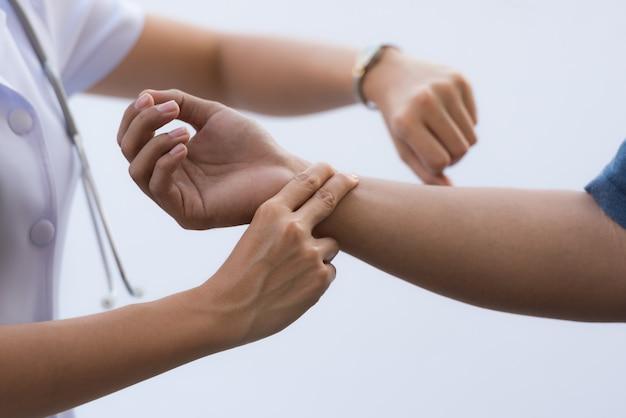 Enfermera que controla el pulso paciente a mano, medicina tradicional china.