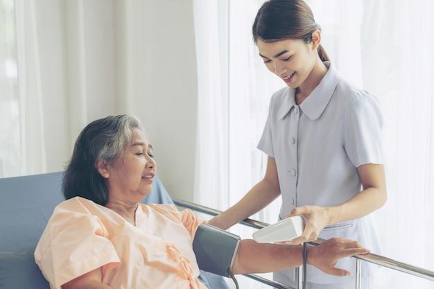 Enfermera que mide la presión arterial de una anciana mayor en pacientes en cama de hospital - concepto senior médico y sanitario