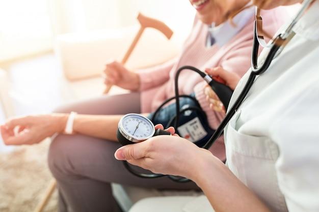 Enfermera que mide la presión arterial de la mujer mayor en casa. joven enfermera medir la presión sanguínea de una anciana en casa.