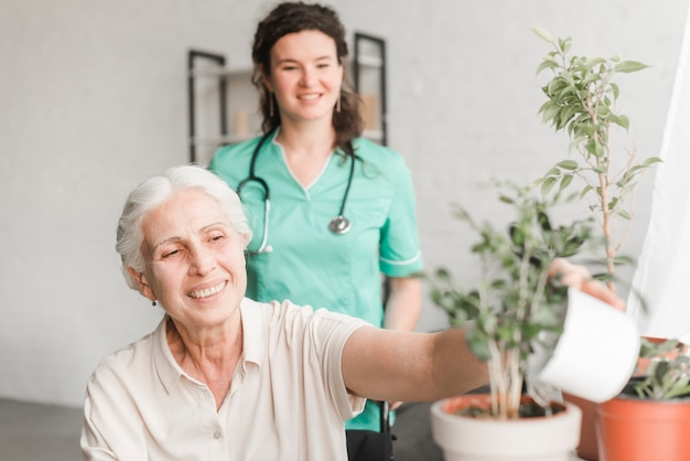 Enfermera que mira a la mujer mayor que se sienta en la silla de ruedas que riega la planta