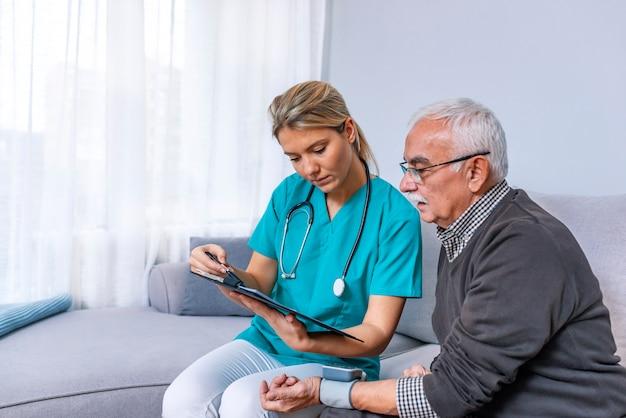 Enfermera que visita al hombre mayor para el chequeo.