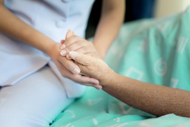Enfermera sentada en una cama de hospital junto a una mujer mayor ayudando las manos