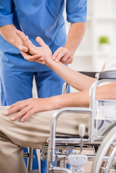 Enfermera de sexo masculino que toma pulso del paciente mayor en el hospital.