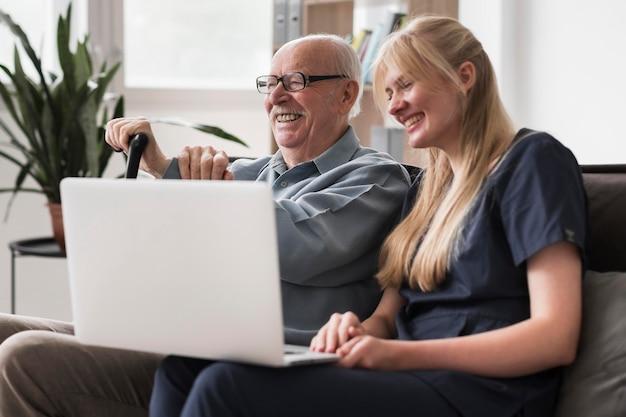 Enfermera sonriente y anciano usando laptop