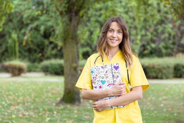 Enfermera sonriente joven con una carpeta de corazones en sus manos