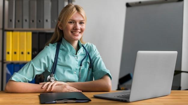 Enfermera sonriente en la oficina con estetoscopio y portátil