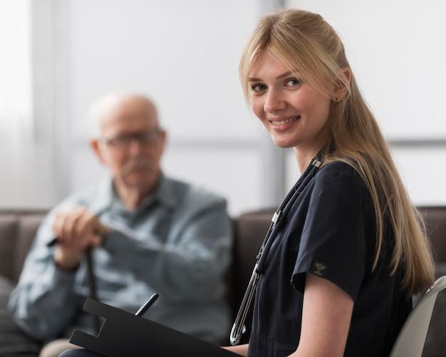 Enfermera sonriente posando con el hombre en un hogar de ancianos