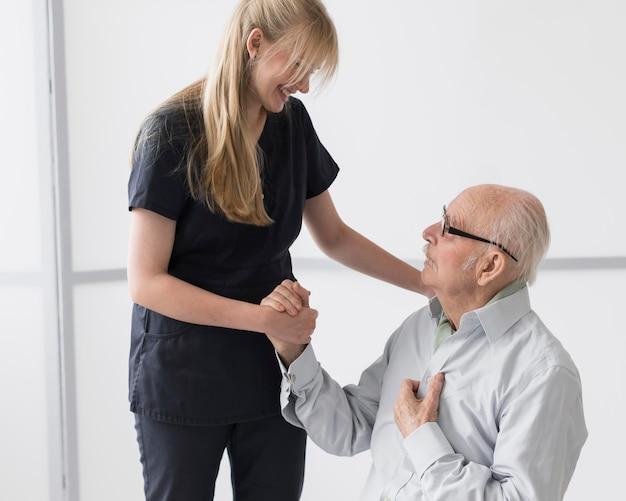 Enfermera sosteniendo la mano del anciano y tranquilizándolo