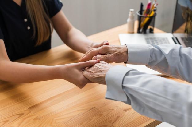 Enfermera sosteniendo las manos del hombre mayor