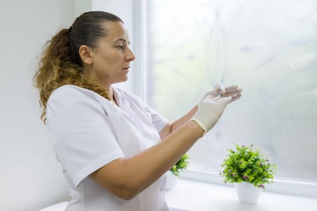 Enfermera sostiene una jeringa, se prepara para una inyección