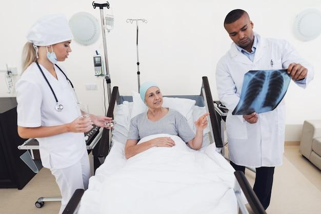 La enfermera sostiene una píldora y un vaso de agua en sus manos.