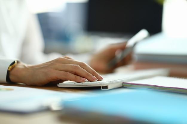 Enfermera tipo texto. mujer en bata blanca sostenga su mano en el teclado blanco.