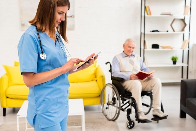 Enfermera de tiro medio revisando su tableta