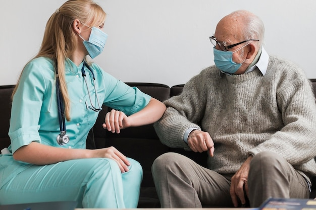 Enfermera tocando el codo anciano durante la pandemia