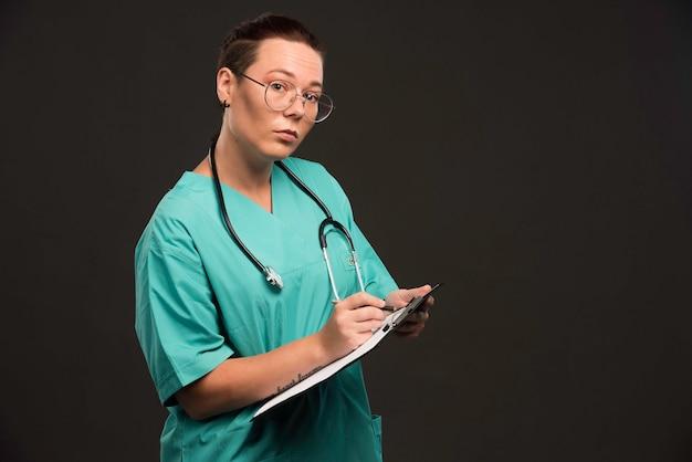 Enfermera en uniforme verde sosteniendo el espacio en blanco y escribiendo la historia.