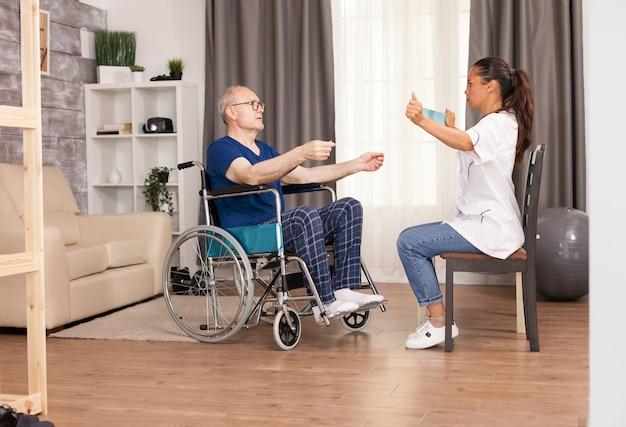Enfermera usando banda de resistencia y explica al anciano cómo usarla.