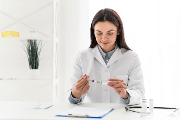 Enfermera vertiendo la vacuna en una jeringa