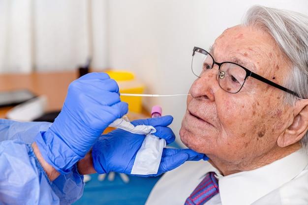 Enfermera vestida con traje protector de coronavirus y máscara, realizando una prueba de coronavirus en un anciano.