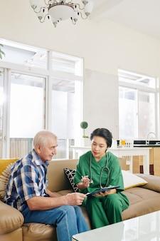 Enfermera visitando paciente anciano en casa