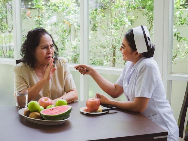 Las enfermeras están alimentando manzanas a los ancianos, las mujeres mayores no quieren comer fruta