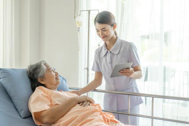 Las enfermeras están muy bien atendidas. los pacientes de edad avanzada en cama de hospital sienten felicidad.
