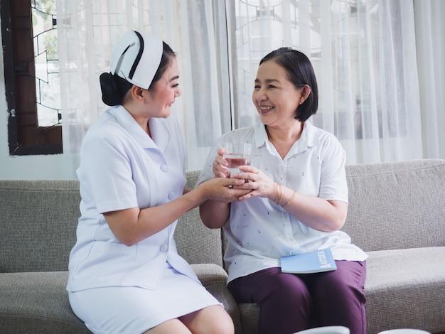Las enfermeras llevan agua a los ancianos para beber.