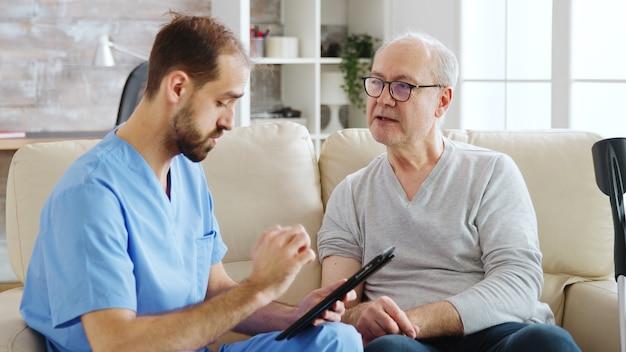 Enfermero caucásico hablando con un paciente de un hogar de ancianos sobre su salud. la enfermera está tomando notas en una tableta digital.