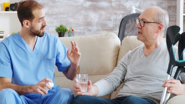 Enfermero dando pastillas a un hombre jubilado en un hogar de ancianos.