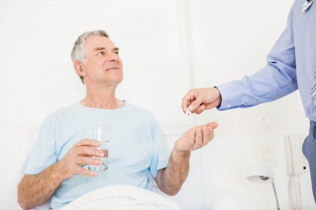 Enfermero dando píldoras al hombre mayor en el dormitorio