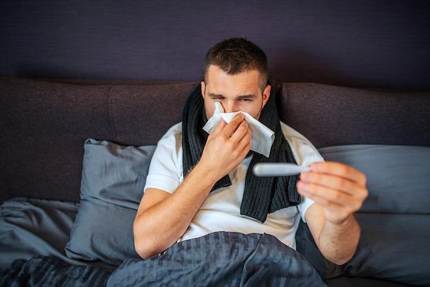 Enfermo joven mira en el termómetro y estornudando en una servilleta blanca al mismo tiempo. su parte baja del cuerpo está cubierta con una manta. joven tiene bufanda alrededor del cuello.