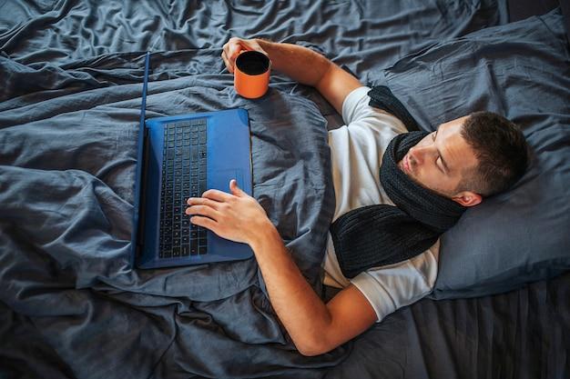 Enfermo joven trabaja en casa. él mira la pantalla de la computadora portátil y toma la mano del teclado. guy sostiene una taza de té caliente con otra mano. él está tranquilo y concentrado.