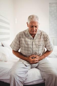 Enfermo senior hombre que sufría de dolor de estómago sosteniendo su estómago en el dormitorio